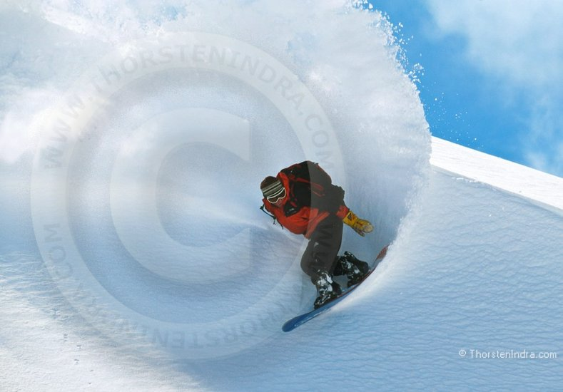 Photo of Snowboarder in fresh powder. Freeride Snowboarding off the beaten track, making tracks where no one has gone before.