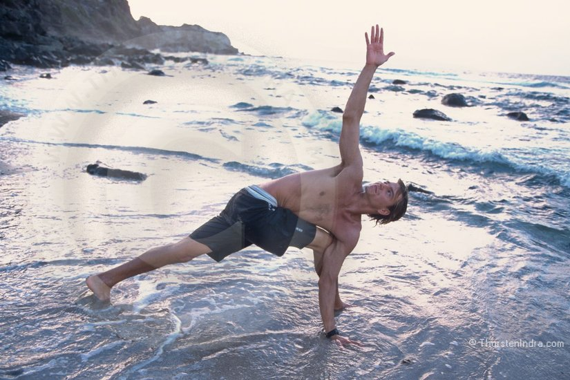 Francisco Goya doing yoga stretching exercises on the beach in Maui/ Hawaii