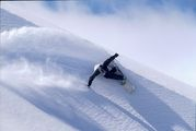 Snowboarder Holger Feist enjoying some fresh powder in Lebanon, making a powerful turn.