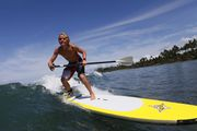 Watershot of SUP Standup Paddle boarding - surfing the waves in Maui/ Hawaii